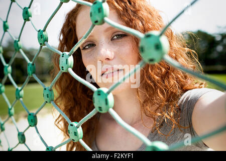 Portrait of redheaded teenage girl looking through net - Stock Photo