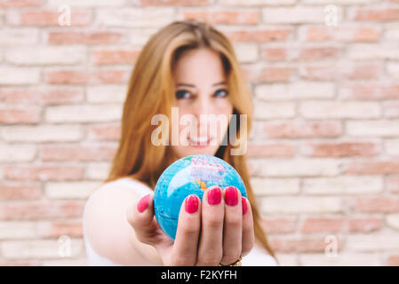 Young woman holding a globe in her hand - Stock Photo