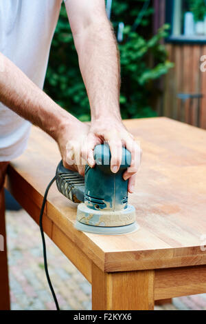 Man sanding an oak table with a random orbital sander - Stock Photo