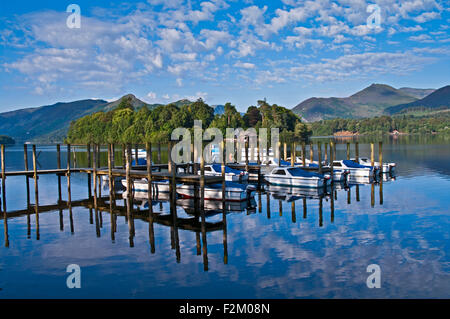 View across small boats moored at jetties on Derwentwater towards wooded Derwent Isle, summer, reflections, Cumbria - Stock Photo