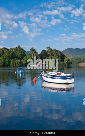 View over small boats moored on Derwentwater to boathouse and jetty on wooded Derwent Island, calm sunny summer - Stock Photo