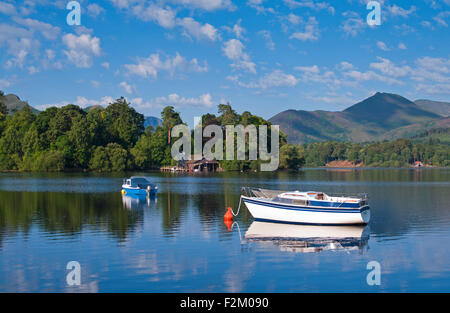 View over small boats moored on Derwentwater to wooded Derwent Island, fells rising behind, calm sunny morning, - Stock Photo