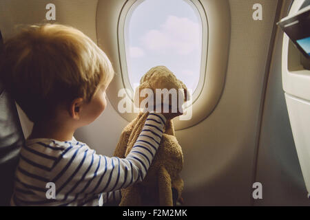 Little boy sitting on an airplane with his soft toy looking through window - Stock Photo