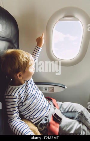 Little boy pointing out of an airplane window - Stock Photo