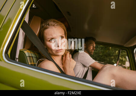Woman in van on a road trip looking out of the window - Stock Photo