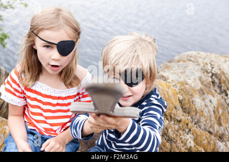 Boy and girl dressed up as pirates at a rock - Stock Photo