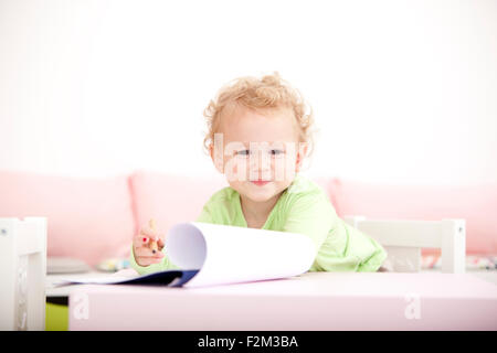 Portrait of little blond girl with coloured pencil - Stock Photo