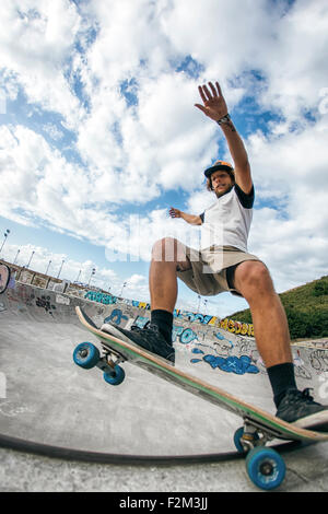 Young man skateboarding in a skatepark - Stock Photo