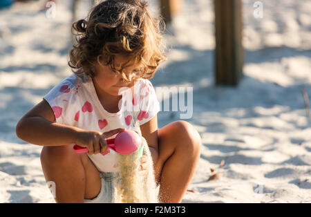 Little girl playing in sandbox on playground - Stock Photo
