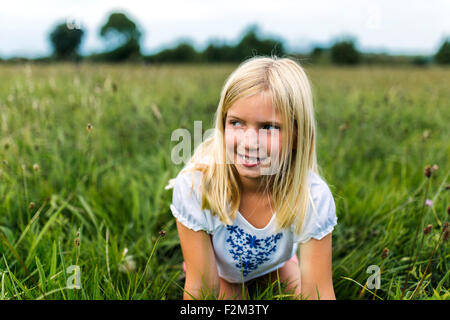 Portrait of girl kneeling on a meadow watching something - Stock Photo