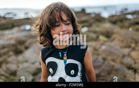 Spain, Gijon, portrait of smiling little boy at rocky coast - Stock Photo