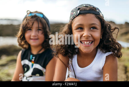 Spain, Gijon, portrait of smiling little girl and her friend in the background sitting at rocky coast - Stock Photo