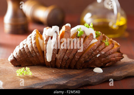 Baked hasselback potatoes with sour cream - Stock Photo