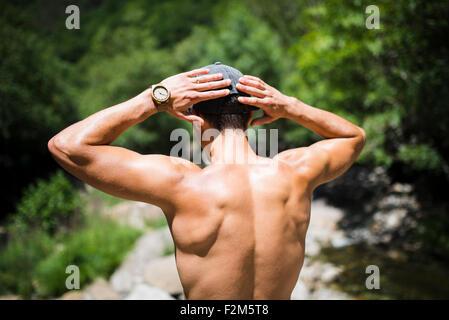 Back of shirtless young man wearing wrist watch - Stock Photo