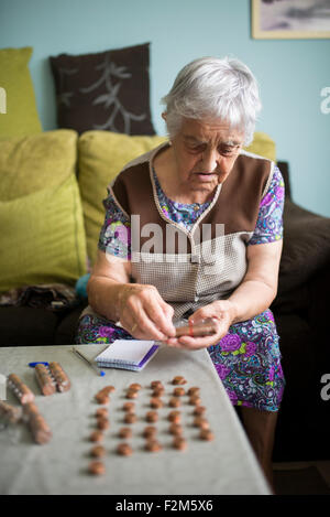 Senior woman sitting on couch at home counting Euro cent coins - Stock Photo