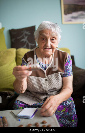 Portrait of senior woman sitting on couch at home showing a package of coins - Stock Photo