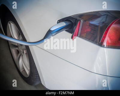 Electric Car Being Charged. Charging an electric car with the power supply plugged in - Stock Photo