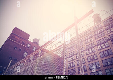 Retro toned old building protected with barbed wire fence, New York, USA. - Stock Photo