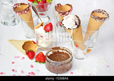 Ice-cream cones with ice-cream, decorated with chocolate and coconut flakes, sugar hearts - Stock Photo
