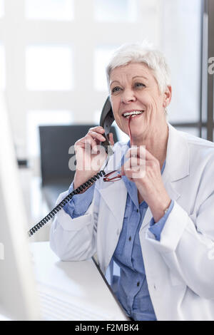 Smiling senior woman in lab coat on the phone - Stock Photo