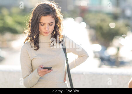 Young woman with cellphone in city - Stock Photo
