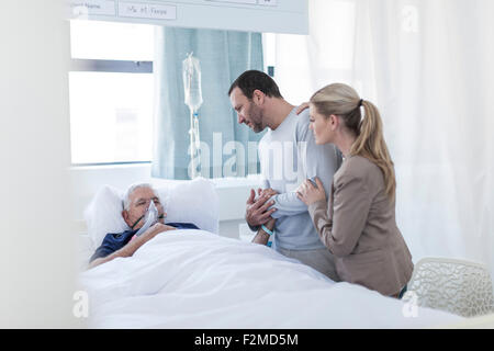 Couple visiting senior patient in hospital - Stock Photo