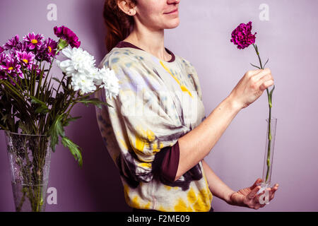 Young woman with a single flower in her hand - Stock Photo