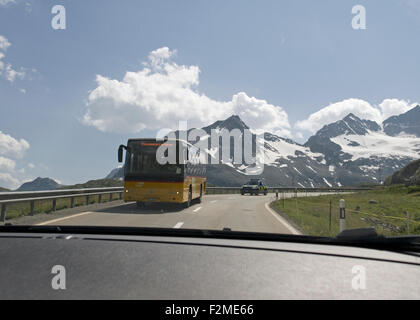 public transport bus on mountain road seen from a car near the border between Switzerland and Italy in Grisons canton - Stock Photo