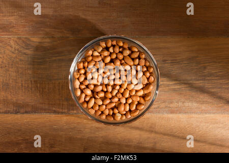 peanuts in a bowl on wood background - Stock Photo
