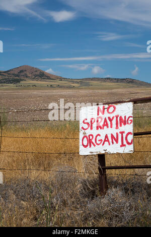 Promontory, Utah - A sign at a farmer's field warns against spraying because the farm is organic. - Stock Photo