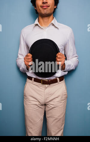 Young man standing by a blue wall with a hat - Stock Photo