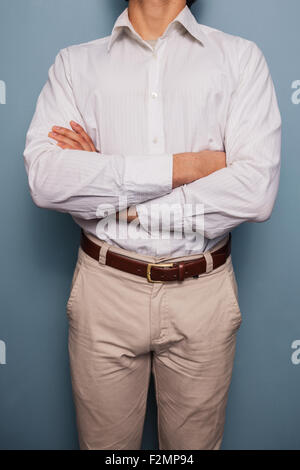 Young man standing by a blue wall with arms crossed - Stock Photo
