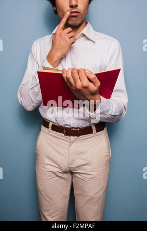 Young man standing by a blue wall reading book - Stock Photo