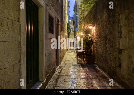 Narrow and empty alley with few cafe tables at the old town in Split, Croatia, at dark after rain. - Stock Photo