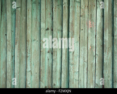 Detail of the old fence from wooden planks covered with green paint peeling off. - Stock Photo