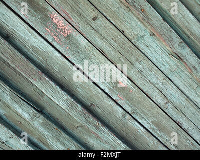 Diagonal view of the old fence from wooden planks covered with peeling green paint - Stock Photo