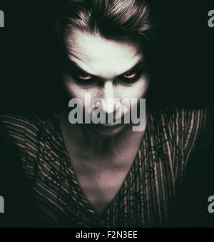 Face of scary woman with evil eyes in the dark - Stock Photo