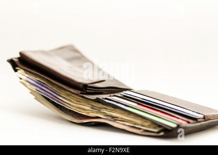Open dark brown leather wallet crammed with banknotes and plastic credit cards on plain white background. Appears - Stock Photo