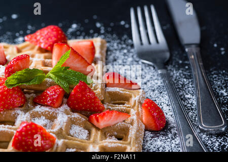Homemade Waffles with fresh Strawberries (on dark background) - Stock Photo