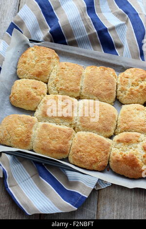 Freshly baked Homemade scones in a baking tray on a wooden board