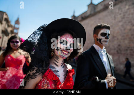 A young couple, costumed as 'La Catrina', walks through the town during the Day of the Dead festivities in Morelia, - Stock Photo