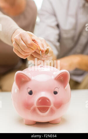 close up of hands putting coin money to piggy bank - Stock Photo
