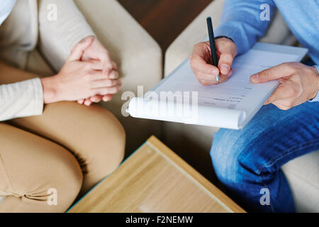 Hands of psychiatrist filling in medical document with patient near by - Stock Photo