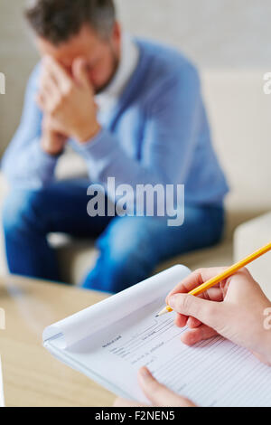 Hands of psychiatrist filling in medical document in front of stressed patient - Stock Photo