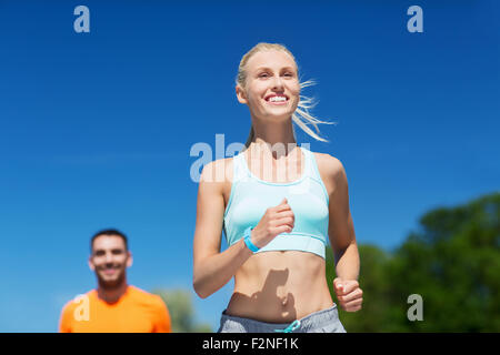 smiling couple running outdoors - Stock Photo