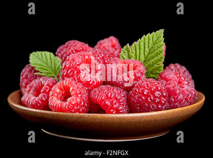Raspberry fruit in plate isolated on black - Stock Photo