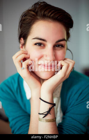 Close up of woman resting chin in hands - Stock Photo