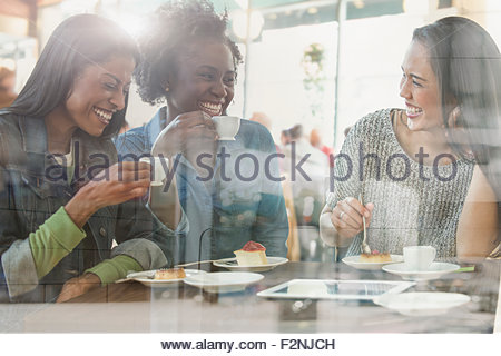 Women drinking coffee in cafe - Stock Photo