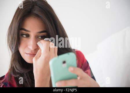 Sad woman crying and using cell phone