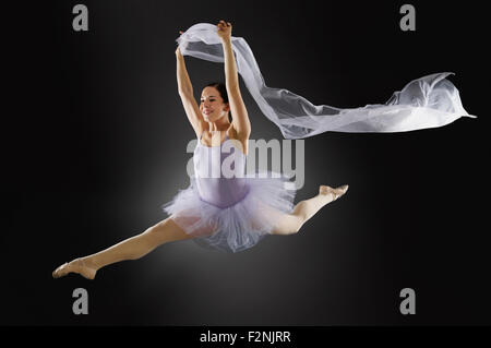 Hispanic ballet dancer leaping in mid-air - Stock Photo